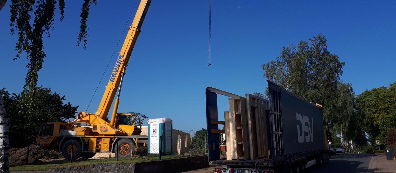 Per LKW werden die vorgefertigten Bauteile an die Baustelle transportiert.
